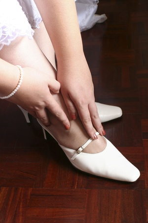 Bride touching her shoes against red wooden floor