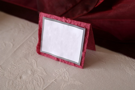 Blank white and red place card on table