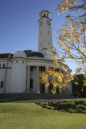 Church with clock tower agianst blue sky and yellow leaves, South Africa