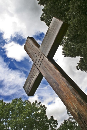 treetops: Wooden cross against treetops and cloudy blue sky
