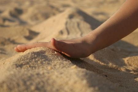 Childs hand playing in white sand on beach