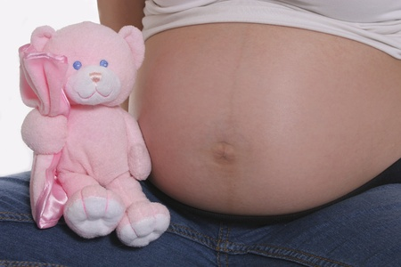 Pregnant belly with pink teddy bear against white background Stock Photo