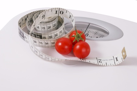 Three red tomatoes and measuring tape on scale