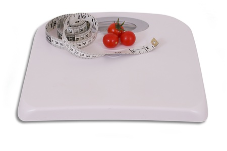 Three cocktail tomatoes and measuring tape on scale Stock Photo