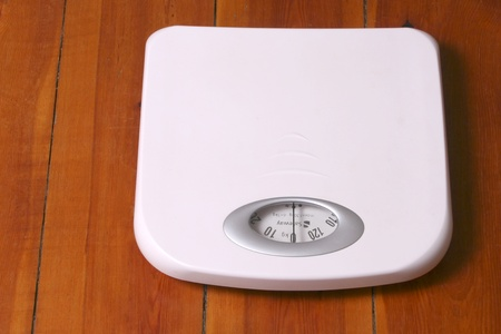 White bathroom scale placed on wood floor Stock Photo