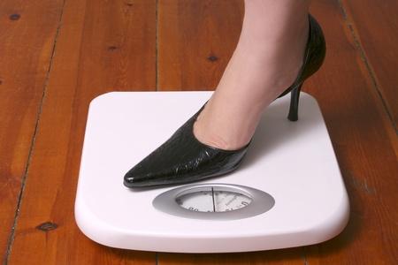 Stilleto foot on white bathroom scale on wood floor Stock Photo - 9304693
