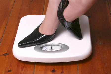 Feet in black stilletoes on a white bathroom scale