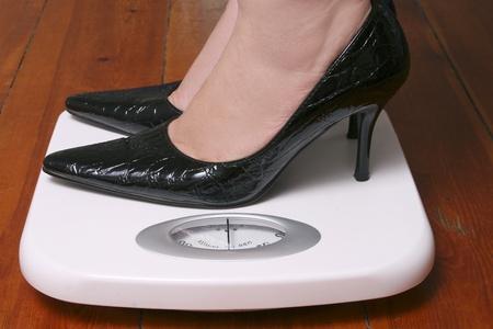 Lady wearing black stilletoes on bathroom scale Stock Photo - 9304694