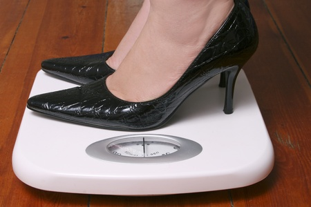 Lady wearing black stilletoes on bathroom scale Stock Photo