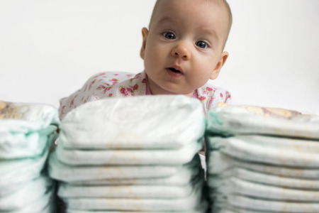 girl care: Adorable baby girl looking over a stack of diapers