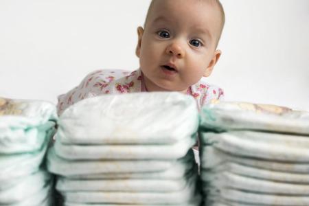 bebe gateando: Muchacha adorable beb� que mira a trav�s de una pila de pa�ales Foto de archivo