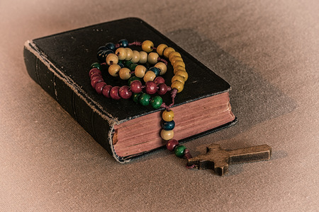 redeem: Wooden rosary and prayer book. White vignette.