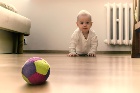 Baby on the floor is going to crawl towards the ball. Stock Photo