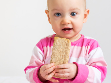Infant eating  a slice of healthy, crunchy bread photo