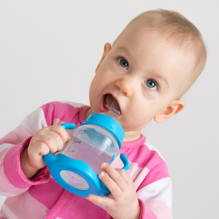 6 12: Adorable baby girl drinking water from the bottle.