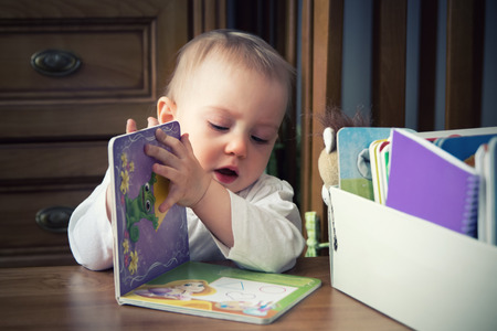 browses: one-year-old baby girl  browses book with interest. Stock Photo