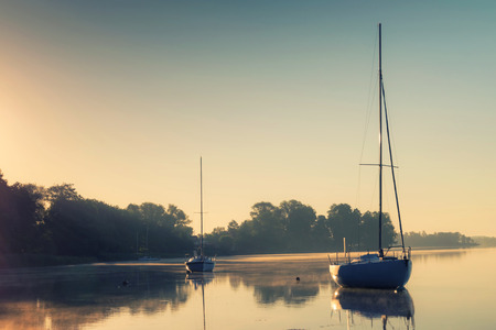 Little sailing boats reflect in  the serene water during sunrise. Stock Photo