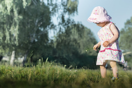 explores: One-year old girl  just walking explores the world. Stock Photo