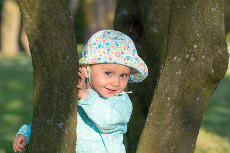 between: Cute, one-year-old smiling baby girl outdoors. She poses among the trees.