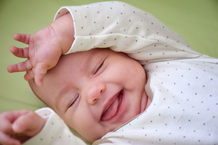 chuckle: Three-month old smiling baby-girl puts the hands up.