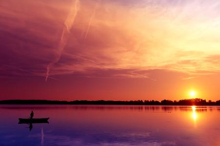 masuria: Fisherman catching fish at sunset. Masuria, Poland.