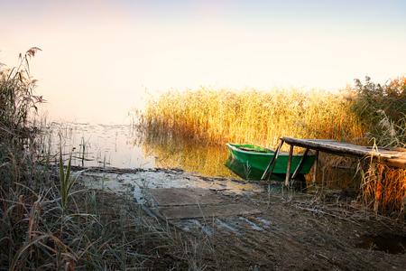 masuria: frosted footbridge with a moored boat. Masuria, Poland. Stock Photo