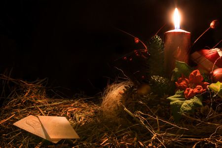 Christmas decoration with wafers and candle. Black background. Stock Photo