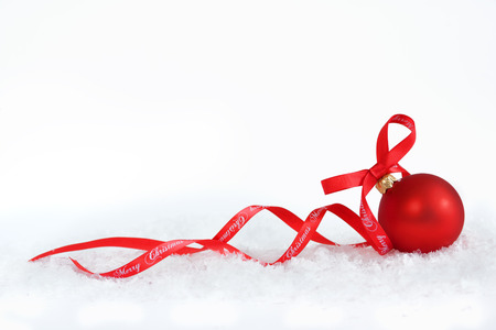 traditional gifts: Christmas ball with red ribbon on artificial snow flakes.