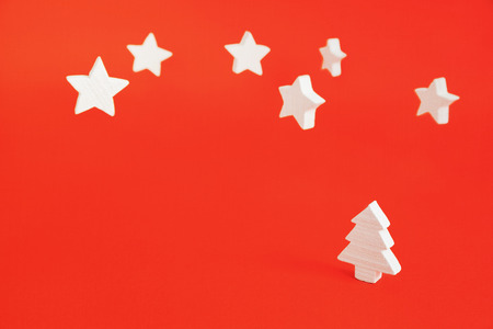 wood blocks: White christmas tree and stars made of wood  on a red background. Stock Photo