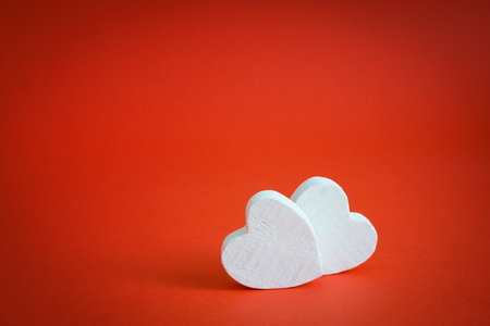 february: White hearts made of wood  on a red background. Valentines day background.