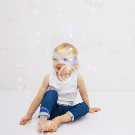joie: Two year old girl has a fun soap bubbles.