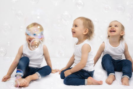 two year: Two year old girl has a fun soap bubbles. Multiple exposure. Stock Photo