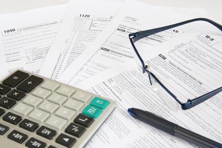 US tax forms with calculator,  glasses and pen.