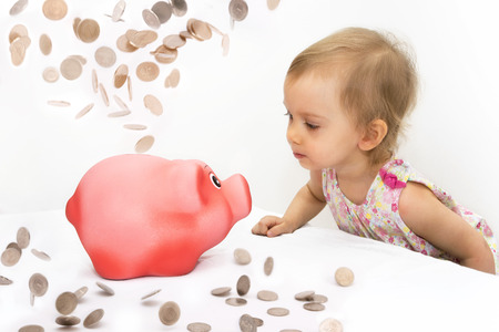 Two-year old girl looks at piggy bank, thinking what to buy for savings. Banco de Imagens