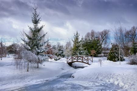 scene season: Snowy, wooden bridge over frozen pond. Poland. Stock Photo