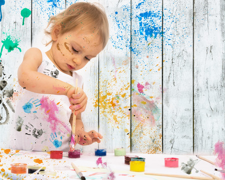 girl studying: two-year old girl paints with poster paintings. Stock Photo