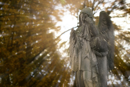 angel cemetery: Crying angel statue at old cemetery in autumn. Double exposure.