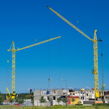 buildingsite: Two cranes on constuction site.