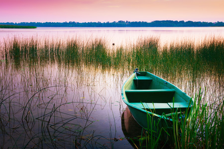 waters: Rowing boat floating over the Lake Lasmiady  waters. Masuria, Poland.