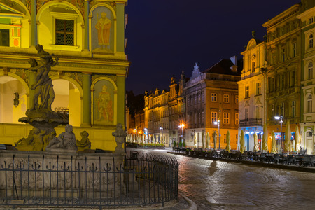 townhouses: Night photo of Poznan Old Town with Prozerpins fountain, beautifully decorated facade of the city hall and numerous highlighted townhouses.