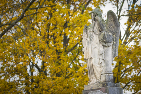 angel cemetery: Crying angel statue at old cemetery in autumn. Mourns those who have died Stock Photo