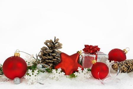 Decoración de Navidad con bolas inferior, copos de nieve, conos y regalo sobre fondo blanco.