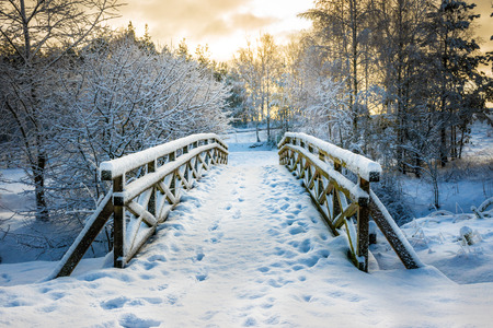 Snowy, wooden bridge in a winter day. Stare Juchy, Poland Stock Photo