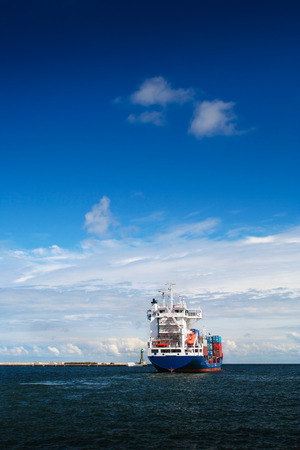 retailer: Cargo ship just leaving Gdynia harbour. Vertical frame.  Poland. Editorial