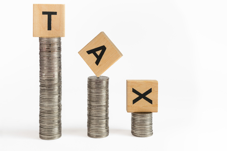 Rows of coin stacks with toy blocks symbolizing taxation. Stock Photo