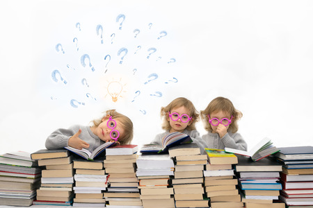 Three little girls ( 3 years old)  in pink glasses. One of them has got an idea.