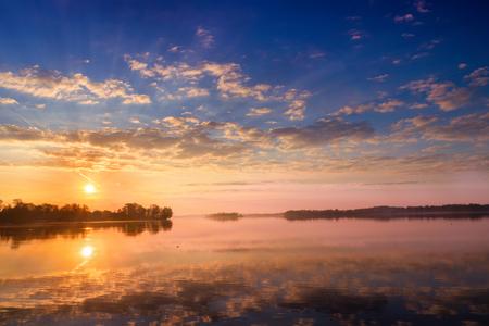 Sunrise with beautiful clouds over Selment Wielki Lake. Masuria. Poland