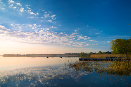 Yachts float on the calm waters of the lake. Early morning. Masuria, Poland . Stock Photo