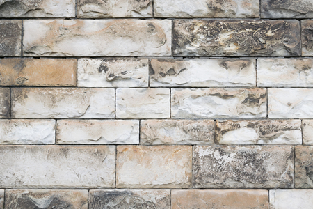 Bumpy ancient wall. Texture of tiles of different sizes. Stock Photo