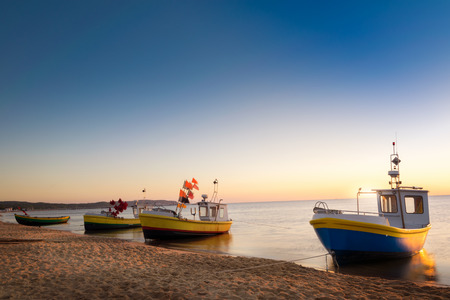 Sun just rises over colorful fishing cutters on sandy beach. Baltic sea, Pomerania. Poland.